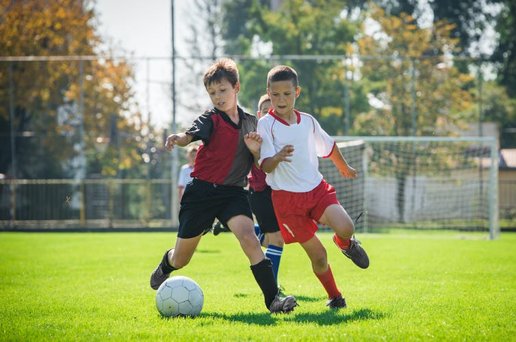 Two boys challenge each other for the ball during a football match.