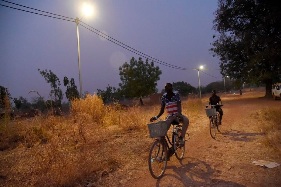 Two cyclists drive past street light poles on a dusty village pathway.