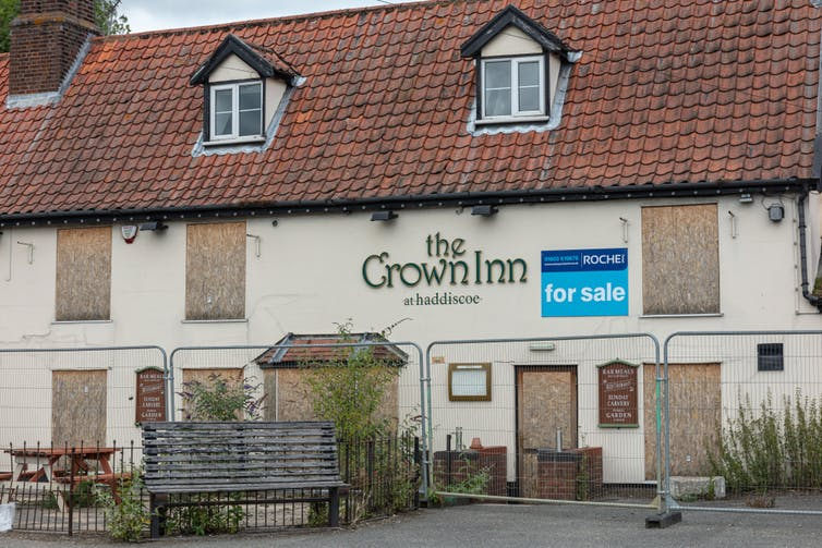Pub with boarded up windows and for sale sign.