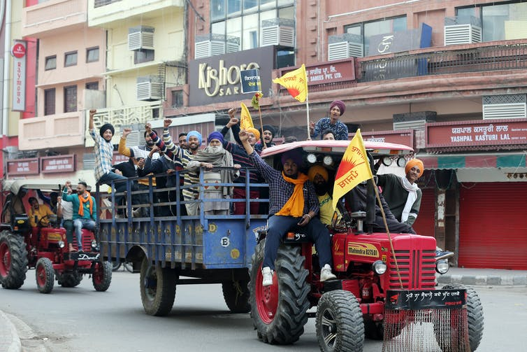 Tractor carrying protesters and flying flags on the streets of Delhi