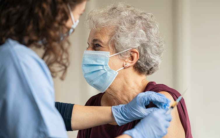 An elderly woman in a mask being vaccinated
