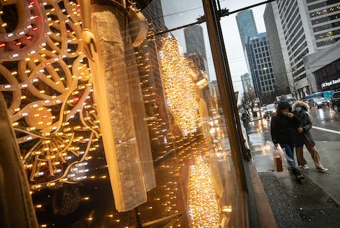 People wearing face masks walk past a store window alit with Christmas lights.
