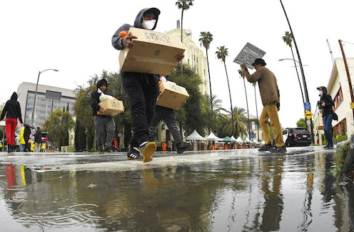 People cross a flooded street with palm trees holding cardboard boxes.
