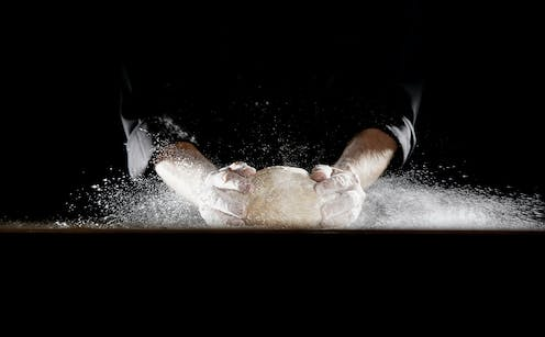 Two hands knead dough against a black background