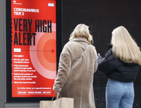 A red sign warning people that they are in a very high alert level area during the coronavirus pandemic.