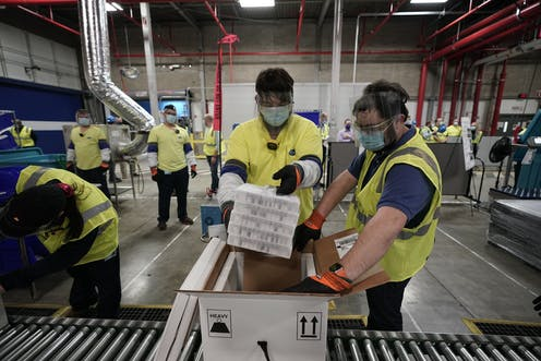 Two workers packing COVID-19 vaccine.