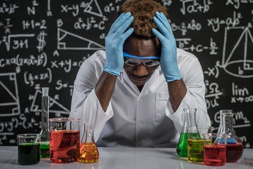 An African American male scientist is stressed out in a lab,