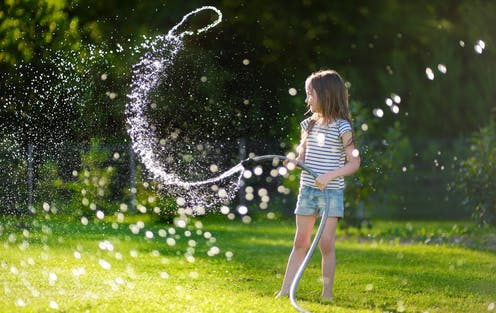 Girl playing with garden hose