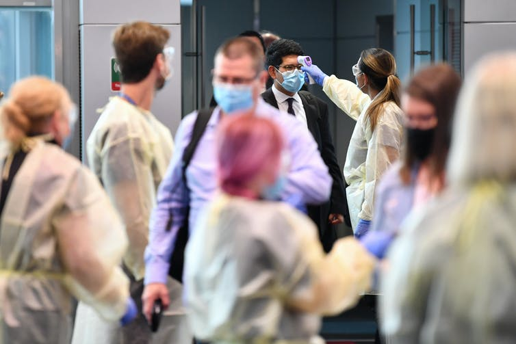 Airport travellers receiving temperature checks