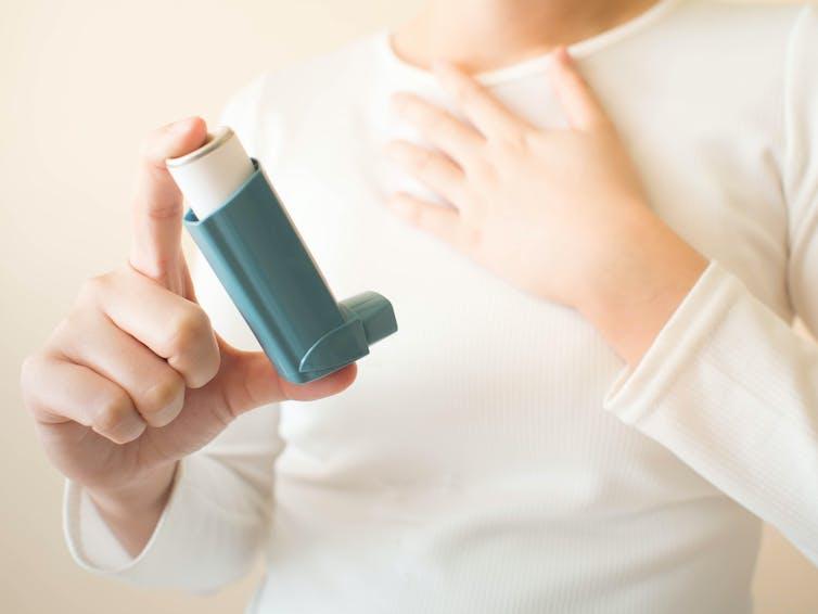A child holding an asthma inhaler