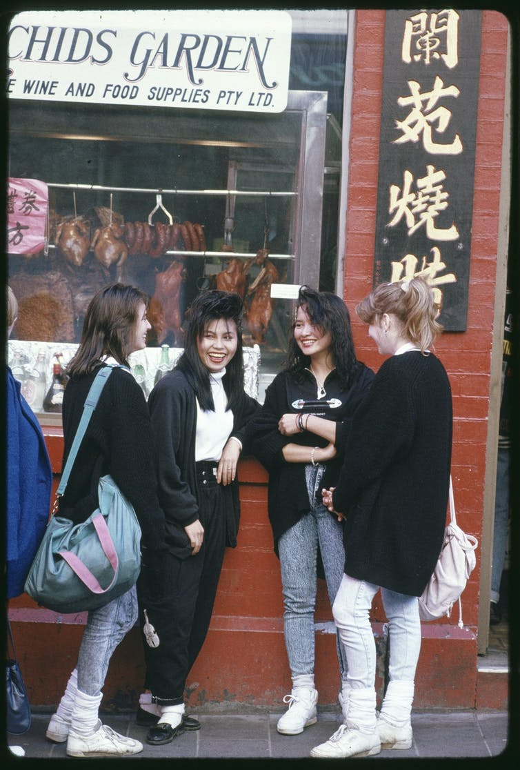 A group of young Asian and white women talking.