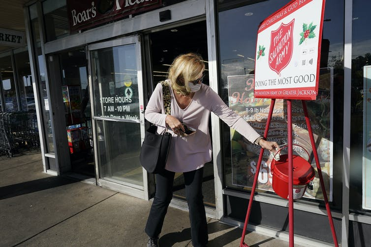 Woman places money into a Salvation Army Christmas appeal bucket.