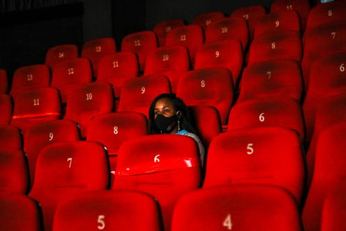 A cinema with red chairs, which are numbered. They are all empty except for one, where a young woman sits wearing a black face mask.