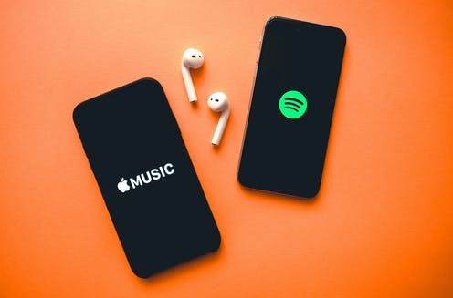 Two phones on orange background with earphones showing apple music logo and spotify logo.