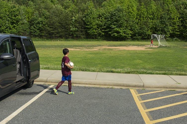 Boy holding ball walks away from car