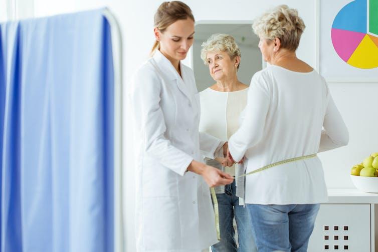 Uma mulher idosa tem sua cintura medida por uma médica.