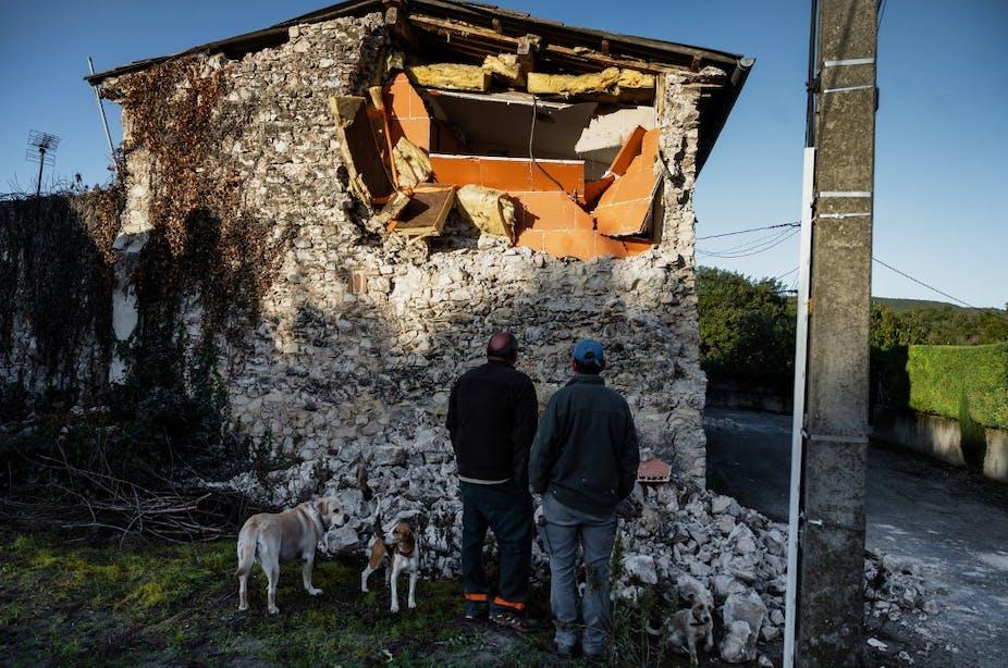 Des gens devant des décombres.