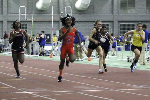 High school athletes run during a track race