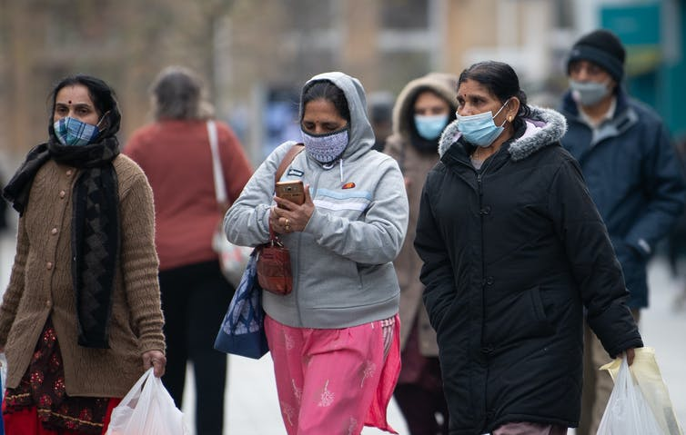 Three women wearing masks walk down the street with shopping bags.