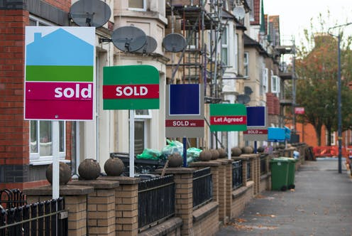 Several sold signs outside a row of houses on a street in the UK