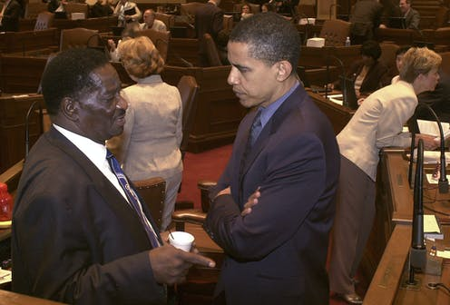 In a photo from 2004, Barack Obama speaks to a fellow Illinois legislator in the state Senate chamber.