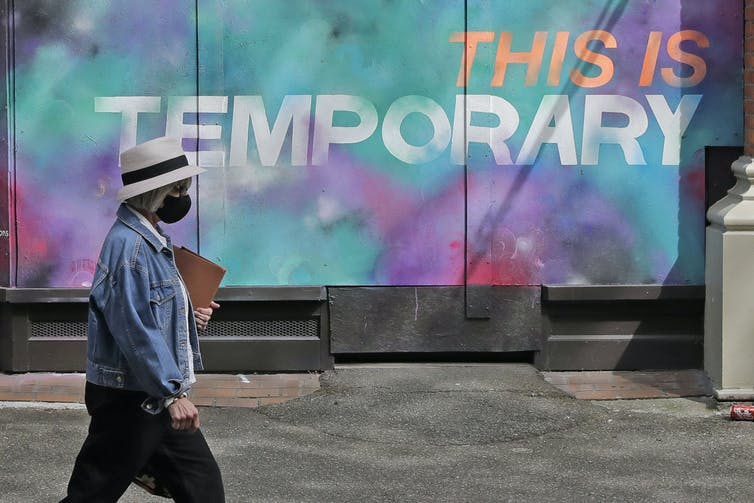A person wearing a mask walks past a mural on a boarded-up window that reads 'This is temporary.'
