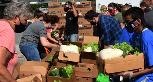 People in masks surrounding boxes of produce