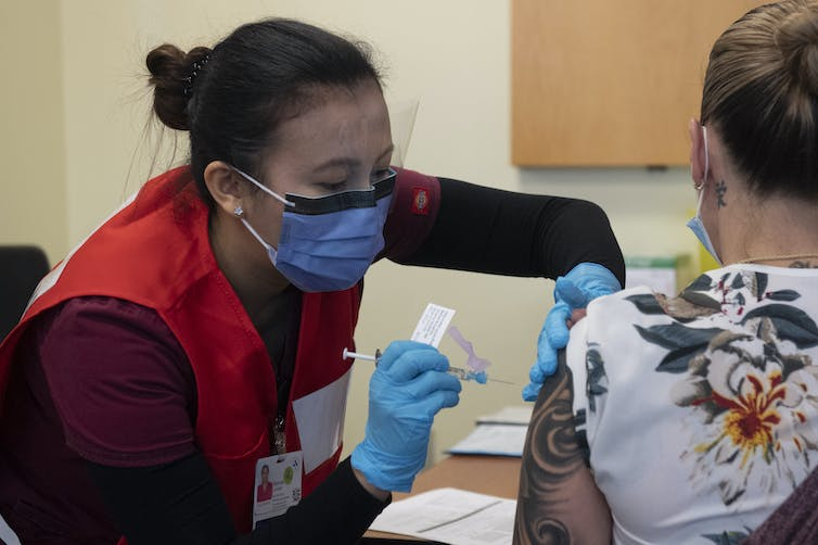 A nurse wearing a mask vaccinates another woman.