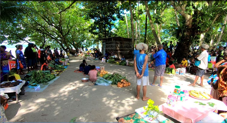 People gather at community markets on tropical atoll island