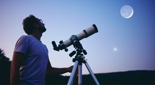 Man with telescope looks up to the sky.