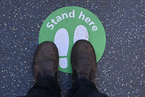 Feet almost (but not quite) standing on a sign marked 'stand here'