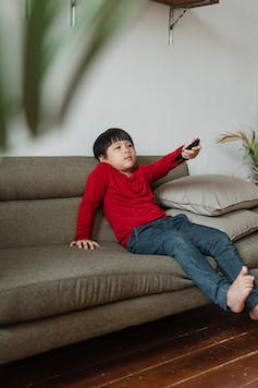 A child on a sofa pointing a remote control.