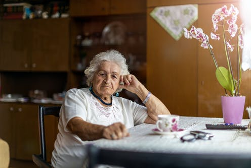 An elderly woman sits at the table at home.