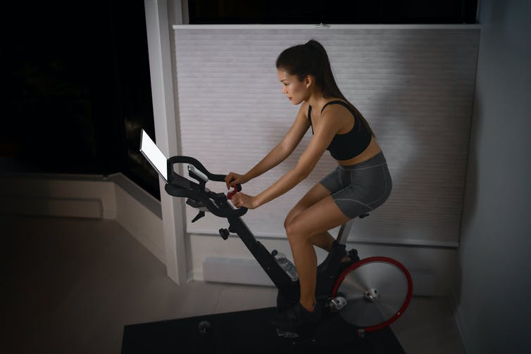 Woman riding a stationary bike while looking at a tablet.