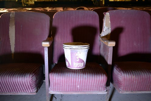 A stack of empty popcorn buckets on a purple chair in an abandoned cinema