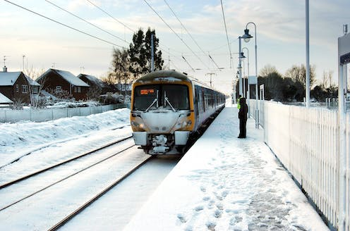 A train pulls into a snowy station with one passenger on the platform.