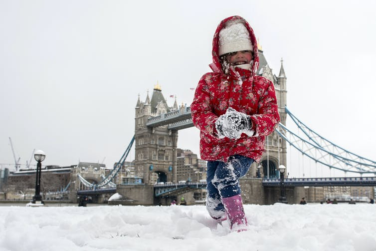 A young girl makes a snowball with London's Tower Bridge in the background.