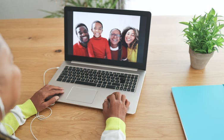 An older woman talking to her family on a video call