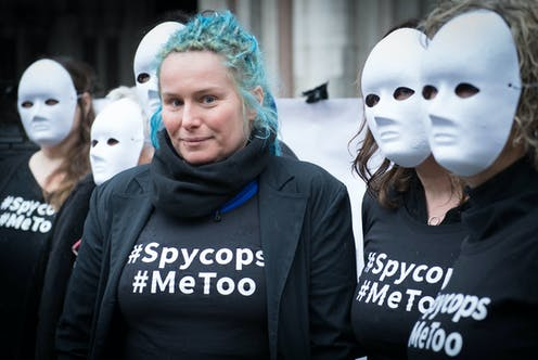 Kate Wilson, a victim of undercover police, standing in a group of other women wearing masjs and wearing wearing 'spy cops' t-shirts