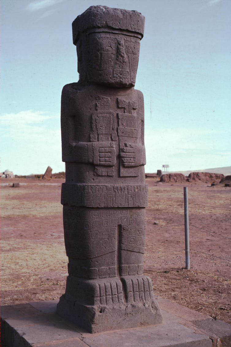 An intricately carved monolith of a person holding an item in each hand.