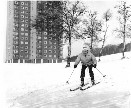 A man in winter attire skis down a snowy hill with a tower block behind him.