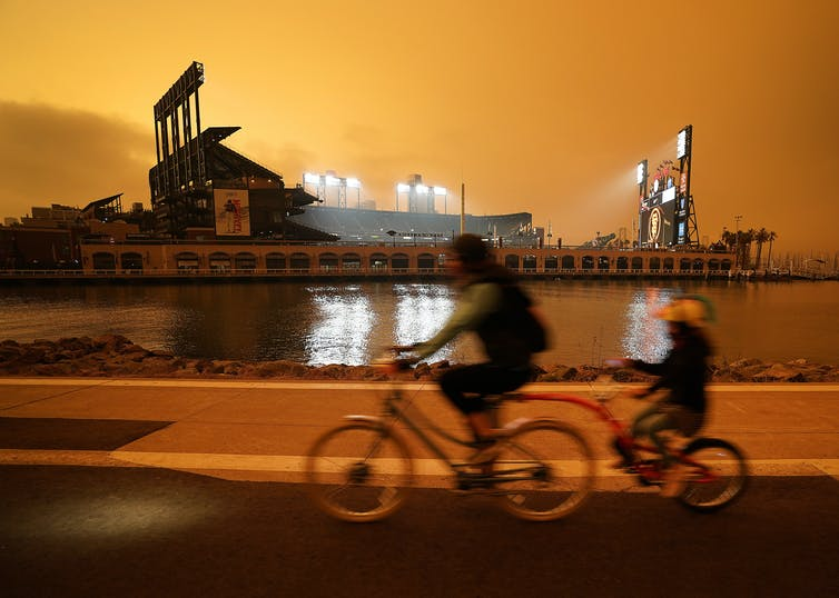 People ride past a ballpark under an orange sky.