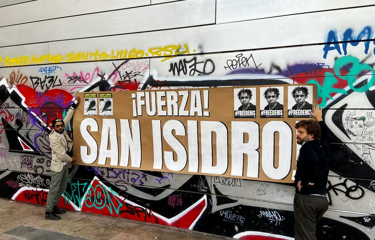 Two men hold la banner reaading 'Fuerza! San Isidro'
