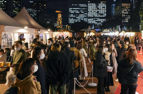 A crowd of people wearing masks attend a Christmas market in Tokyo.