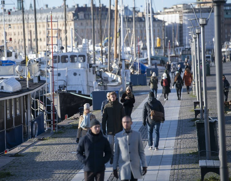 People walk by a dock in Stockholm.