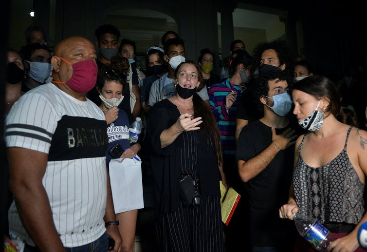 Woman in black wearing a facemask speaks, surrounded by a crowd
