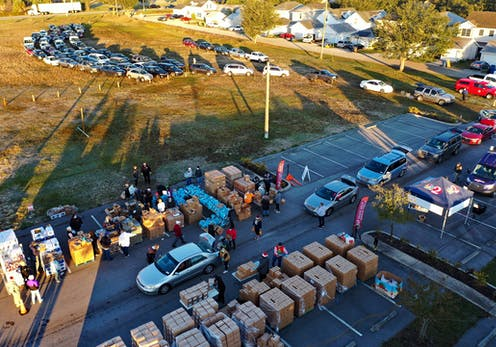 Aerial view of a parking lot with lots of cars and cardboard boxes and people standing around