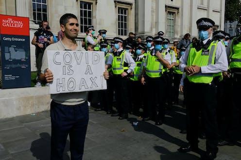 Manifestantes en Londres con pancarta que dice que covid es un bulo.