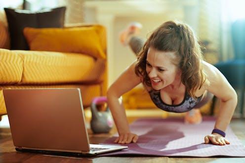 Una mujer hace flexiones en el suelo mientras mira un ordenador.