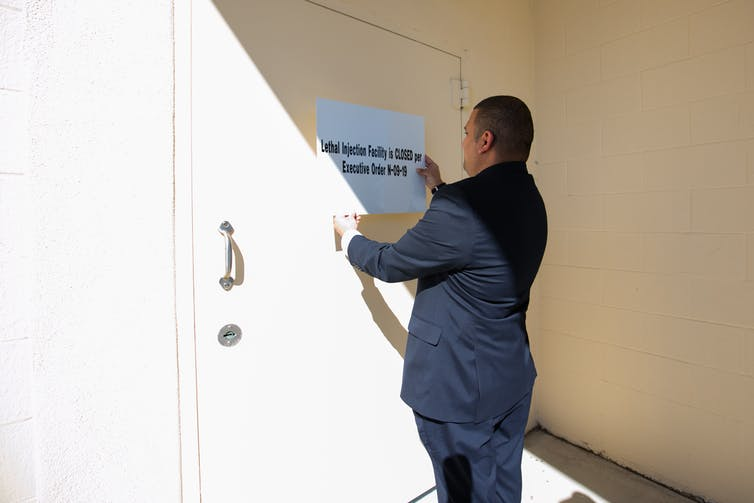 Man stands next to a sign reading that the lethal injection facility is closed due to COVID-19.